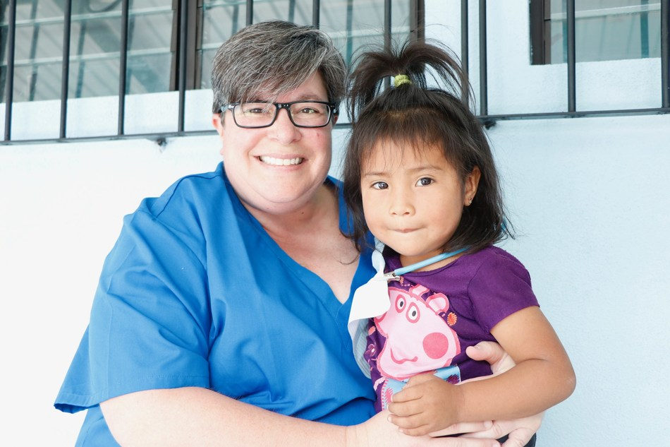 Dental assistant, Tammy Coffey of Aspen Dental-Kentucky shares a special moment with local Guatemalan girl after she received dental care.