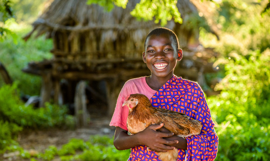A smiling Resheal holds one of his chickens, offspring of one of the chickens his mother received in 2004 from the Gift Catalogue (CNW Group/World Vision Canada)