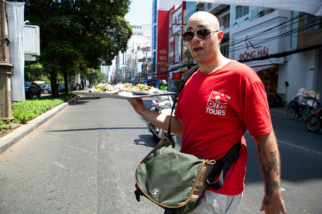Fredrick, Owner of Back of the Bike Tours in Ho Chi Minh City, Vietnam. Bringing Green Papaya Salad across the street to a local park to share with Australian Travellers on his tour.