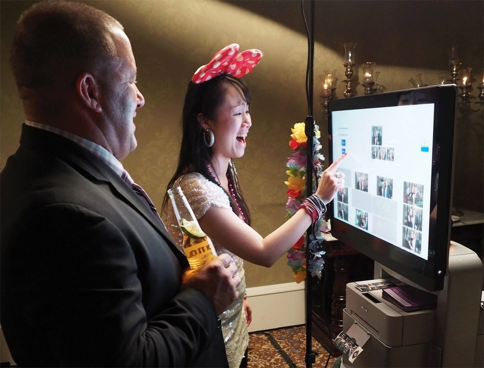 Teams socializing around photobooth at Holiday party. (CNW Group/Tribute Kiosk)
