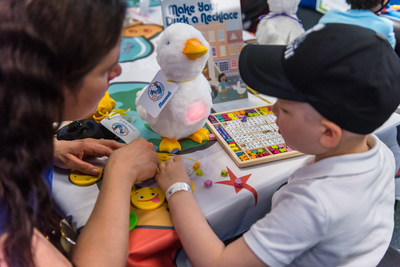 Maxwell, a 4-year-old cancer patient, creates a personalized necklace for his new friend, My Special Aflac Duck, following a fun scavenger hunt at Children's Hospital in New Orleans on Thursday, Nov. 29, 2018. Aflac, a long-time supporter of children and families facing childhood cancer, hosted a special delivery event for several children at the hospital to debut the company's new robotic, caring companion for children coping with cancer.