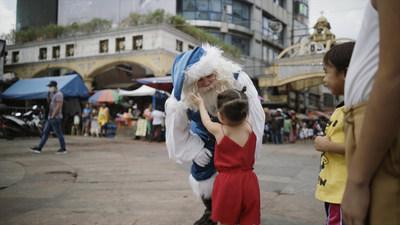Le père Noël bleu en visite à Manille aux Philippines (Groupe CNW/WESTJET, an Alberta Partnership)