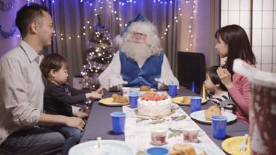 Des gens apprécient leur façon de faire unique lors d'un festin traditionnel des Fêtes en compagnie du père Noël bleu, à Tokyo, au Japon (Groupe CNW/WESTJET, an Alberta Partnership)