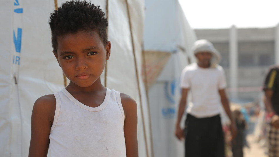 On 4 December 2018 at a camp for internally displaced persons in Aden, Yemen, a child stands outside of their temporary shelter. © UNICEF/UN0262515/Abdulhaleem (CNW Group/UNICEF Canada)