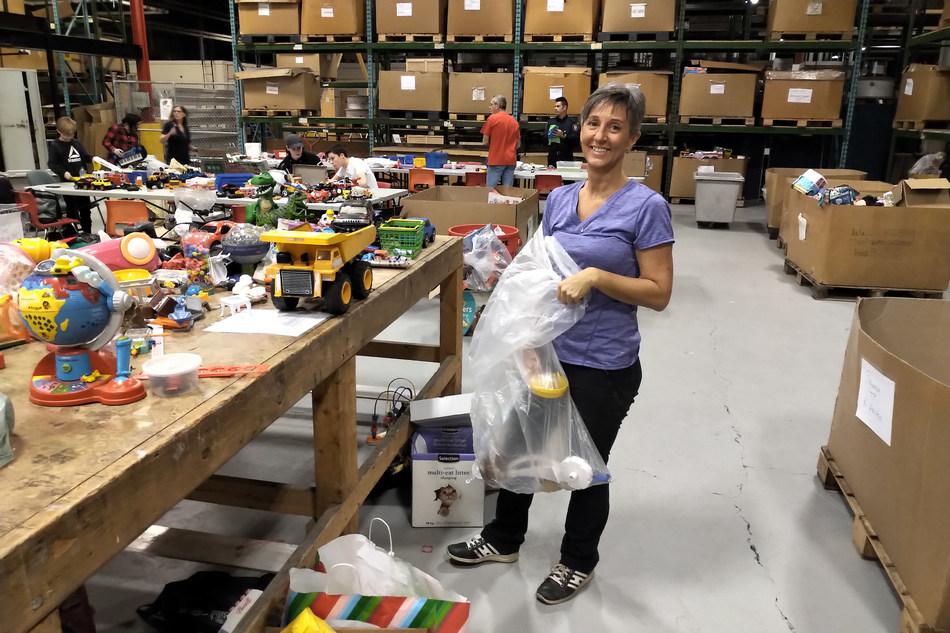 De nombreux bénévoles s'activent au travail, à l'atelier des jouets des pompiers de Montréal, là où les jouets recueillis à longueur d'année auprès du public sont remis à neuf en prévision de la distribution de paniers de Noël et de cadeaux. (Groupe CNW/Association des pompiers de Montréal)