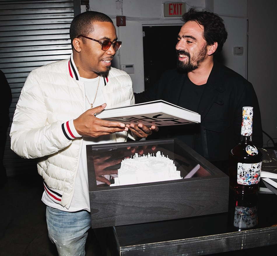 """Urban artist, Alexandre Farto – aka """"Vhils"""" and musician Nas at the 2018 Hennessy Very Special Collector's Edition by Vhils event during Miami's art week on December 5, 2018. The private dinner officially unveiled the Hennessy Very Special Collector's Edition by Vhils – a limited-edition release of 100 unique individually-signed pieces designed using the art-world phenomenon's famed 'Making the Invisible Visible' technique. The new artwork is available on December 6 exclusively on Clos19."""