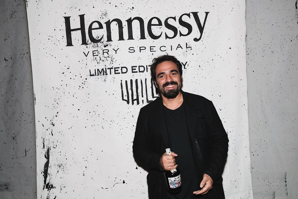 """Urban artist, Alexandre Farto – aka """"Vhils"""" introduces the 2018 Hennessy Very Special Collector's Edition by Vhils at Wynwood Walls in Miami on December 5, 2018. Part of Art Basel Miami, the artist debuted his first Wynwood Walls solo show– 'Ethereal' – before unveiling a limited-release of 100 unique individually-signed pieces for Hennessy, created using the artist's famed 'making the invisible visible' technique. The new artwork is available on December 6 exclusively on Clos19."""