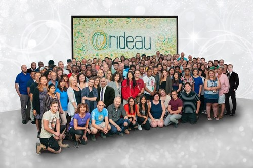 Members of the Rideau staff gather in front of artwork created by Peter W. Hart, president and CEO. (CNW Group/Rideau Inc.)