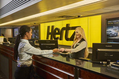 A female Hertz employee reaches across the service counter to hand a female customer keys to a rental car.