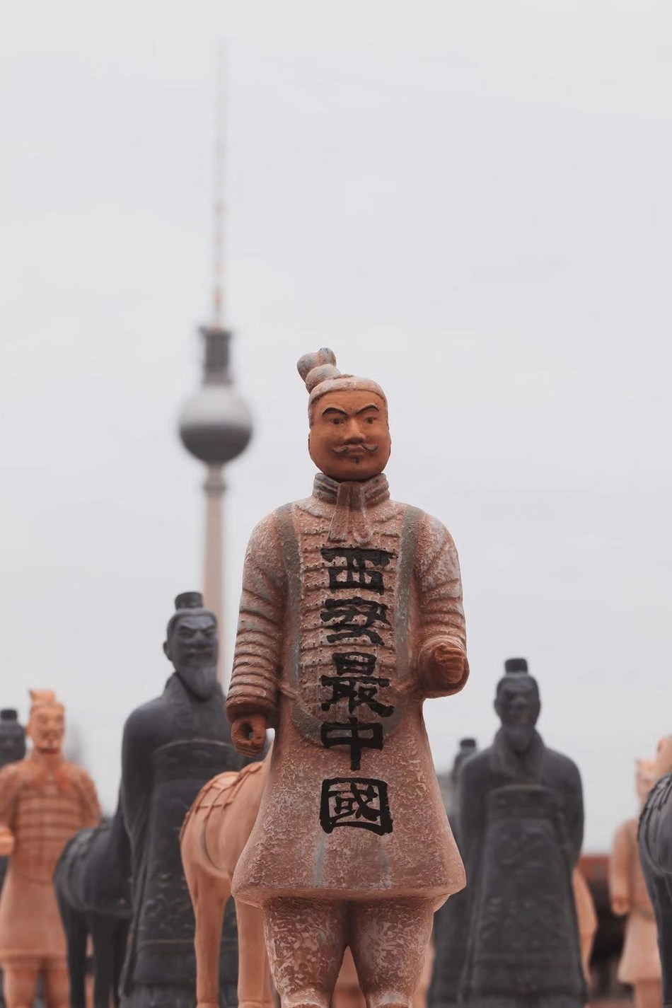 """A terracotta warrior with """"Xi'an Best Representation of China"""" shown in front of notable Berlin landmark, the TV Tower"""