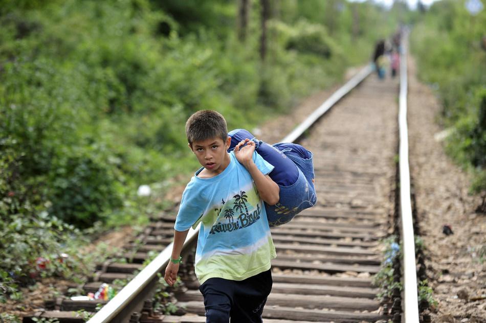 Un garçon, transportant un sac de vêtements sur son épaule, marche le long de la voie ferrée, près de la ville de Preševo, à la frontière qui sépare l'ancienne République yougoslave de Macédoine et la Serbie, en septembre 2015. © UNICEF/UNI196290/Georgiev (Groupe CNW/UNICEF Canada)