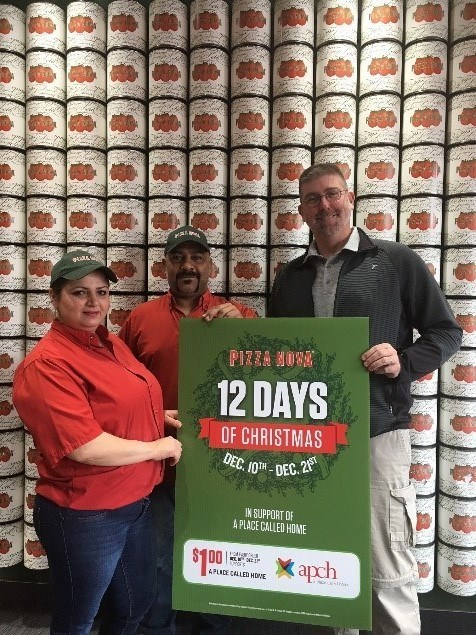 """From left to right: Pizza Nova, Franchisee Khusrau Neikayen """"Sam"""" and his wife Zlata Neikayen along with David Tilley, Manager of Fund Development and Operations, A Place Called Home kicking off 12 Days of Christmas live at Pizza Nova Lindsay on the first day of 12 Days of Christmas. (CNW Group/Pizza Nova)"""