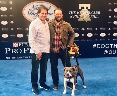 ARF co-founder Tony La Russa (left), stands with veteran and Pets and Vets program graduate David Fuller, and his service dog Katie (right), in the main ring at the National Dog Show Presented by Purina.