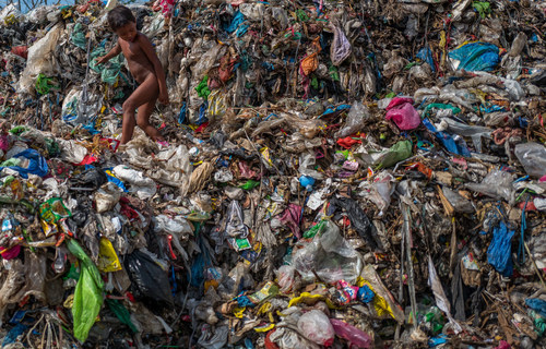 Crédit : Orb Media. Dans une décharge vieille de 50 ans, surplombant l'océan au large de la ville côtière de Dagupan, aux Philippines, un jeune garçon grimpe sur des débris de plastique. La plupart des produits biodégradables ont pourri depuis longtemps, laissant une montagne de plastiques multicolores qui flottent vers la mer sur les vents côtiers.