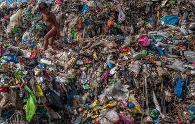 Crédito: Orb Media. Um menininho sobe em restos de plástico num depósito de lixo de 50 anos, à beira do oceano, na cidade marítima de Dagupan, Filipinas. A maioria dos itens biodegradáveis já apodreceu há muito tempo, deixando uma montanha de plásticos multicoloridos que são levados para o mar pelos ventos costeiros