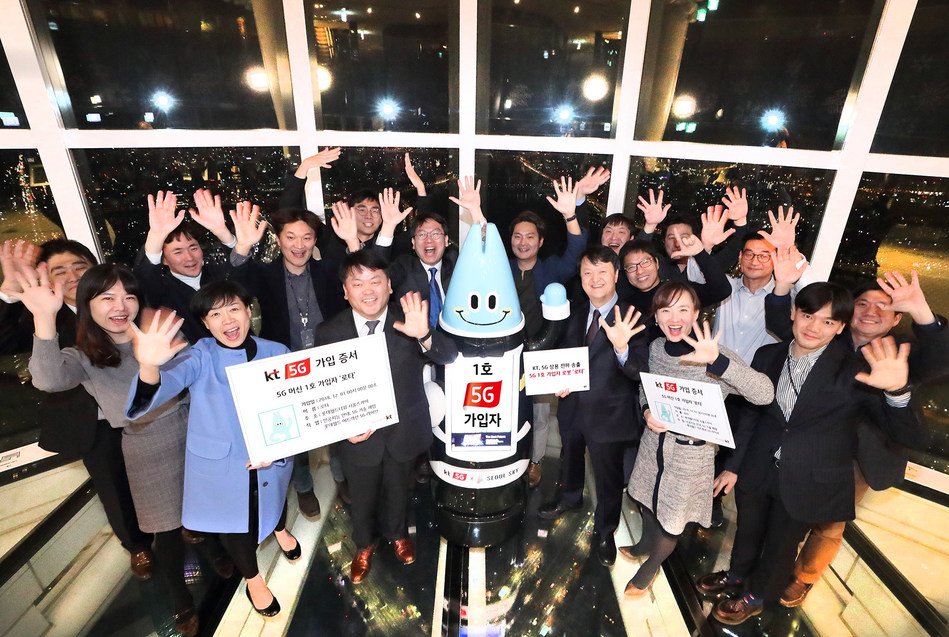Lota, an AI robot and the first subscriber to KT's 5G network commercial service, cheers with KT officials at the Lotte World Tower on December 1.