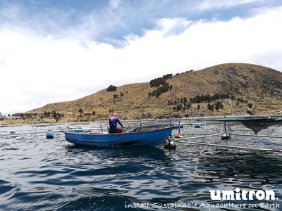 A Peruvian farmer checks his fish via boat, similar boat trips and manual feeding operations will be reduced when using Umitron's automated feeding technology. (PRNewsfoto/Umitron)