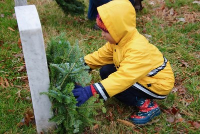 Young child places a wreath at Arlington. Wreaths Across America 2018.