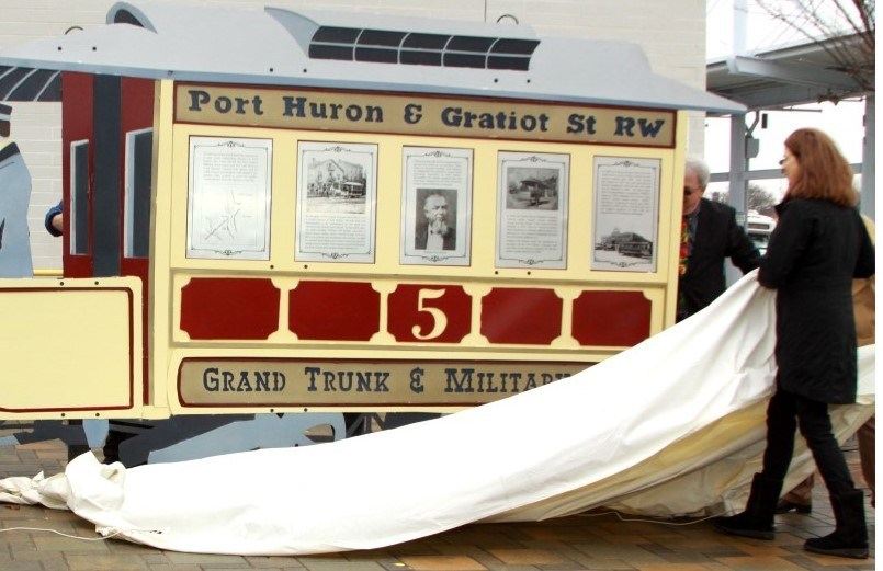 TRANSIT HISTORY UNVEILED: Blue Water Area Transit General Manager Jim Wilson and artist Mino Duffy Kramer unveil a new sculpture that tells the story of transit innovation in Port Huron, Michigan, starting some 150 years ago with William Pitt Edison's horse-pulled trolley service. (photo by Rose Norton)