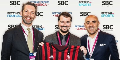The image shows Jaap Kalma, former CCO of AC Milan (left) & Fabio Schiavolin, CEO of  SNAITECH (right) presenting SBC CEO & Founder Rasmus Sojmark (middle) with a signed AC Milan shirt at the Betting on Football 2017 event.