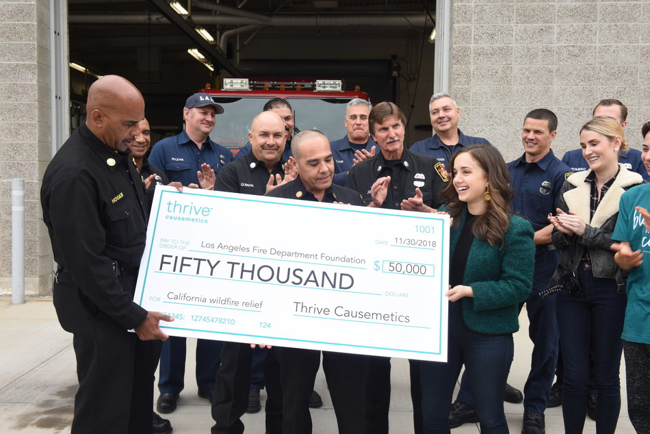 Thrive Causemetics presents $50,000 check to Los Angeles Fire Department Foundation in the wake of devastating Southern California fires. Photo credit: Vivien Best. Pictured (left to right): LAFD West Deputy Chief and Commander Armando Hogan, LAFD firefighters, Karissa Bodnar (CEO and Founder of Thrive Causemetics), Kacki Condatore (online beauty influencer), Clawdeena Tronconi (online beauty influencer)