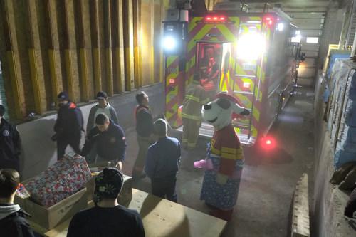 Pompiers et bénévoles s'activent au chargement des paniers de victuailles et des cadeaux distribués aux familles dans le besoin de Montréal. (Groupe CNW/Association des pompiers de Montréal)