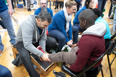 Genesco's Mario Gallione (president of its Journeys division) helps fit students at Nashville's Park Avenue Elementary with new shoes. On Friday, Dec. 14, 200 employees from Genesco set up a mock shoe store and fitted app. 400 students with new shoes and a warm hat for the holidays as part of its 29th annual