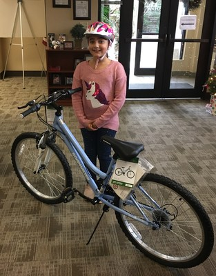 Yanamari Gallagher of Shaw Family Housing picks up her new bicycle donated through the Hunt Heroes Foundation and BrightView Landscapes