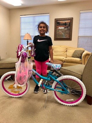 Mikayla Munir of Little Rock Family Housing is all smiles after winning a new bicycle from Hunt Heroes Foundation