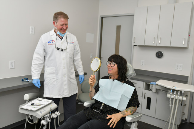 A patient admires the new smile her prosthodontist skillfully crafted by utilizing the latest dental technology and the highest standards of patient care.