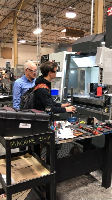 Nick Hackett, President of New Way Air Bearings, shows an eighth-grade student from Delaware County Christian School how one of their machines enables them to create high-precision products utilizing Porous Media Technology™