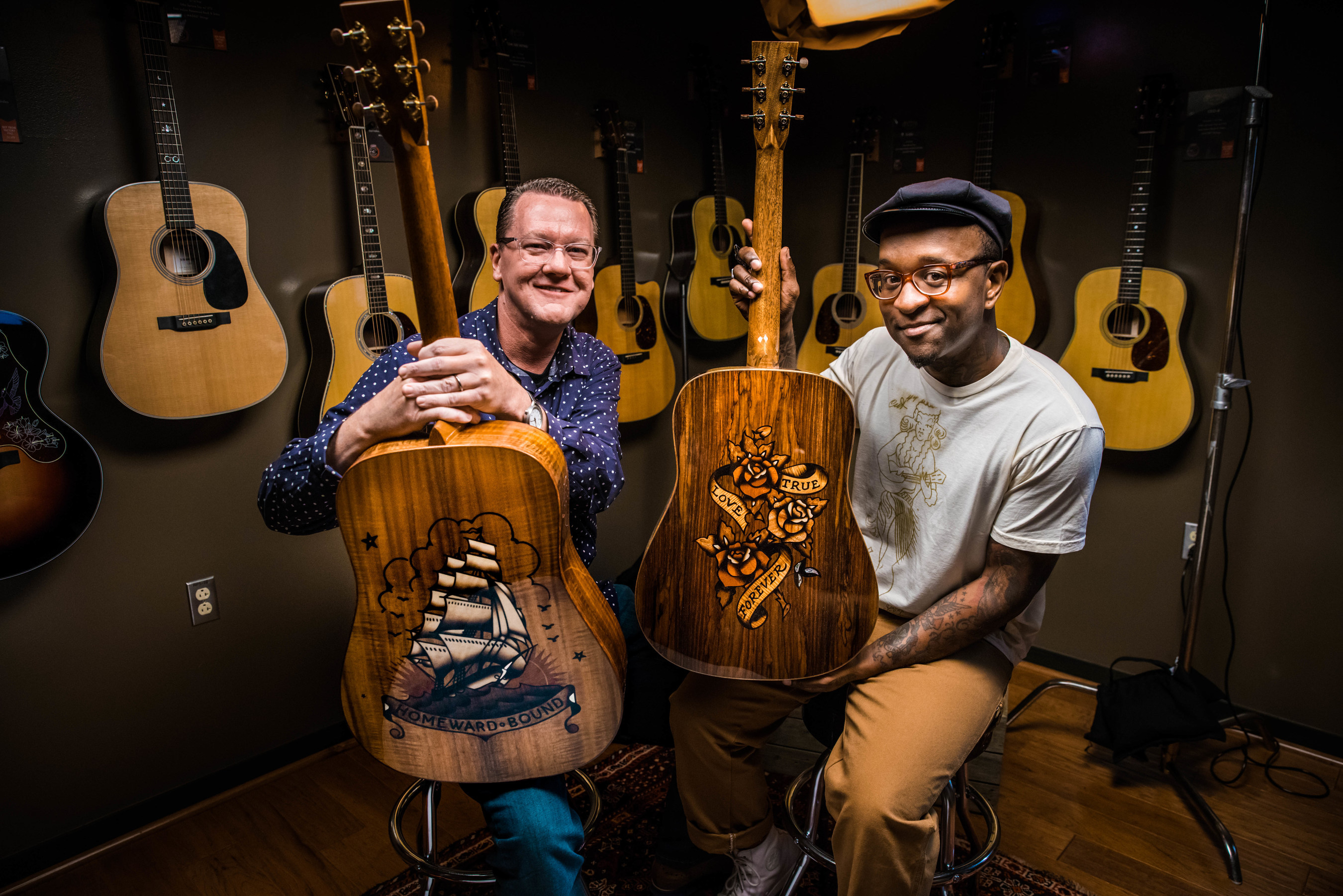 """Scott Sasser (left) of C.F. MARTIN & CO.® and Sailor Jerry Spiced Rum Ambassador, Daniel """"Gravy"""" Thomas (right) showcase the Ink & Wood special edition guitar series."""