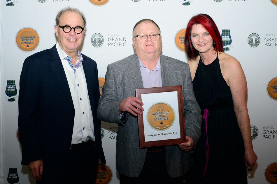 Forty Creek distiller, Bill Ashburn (centre) accepts the award for Whisky of the Year from head judge and awards founder, Davin de Kergommeaux (l), and co-host Heather Leary (r). (CNW Group/Canadian Whisky Awards)
