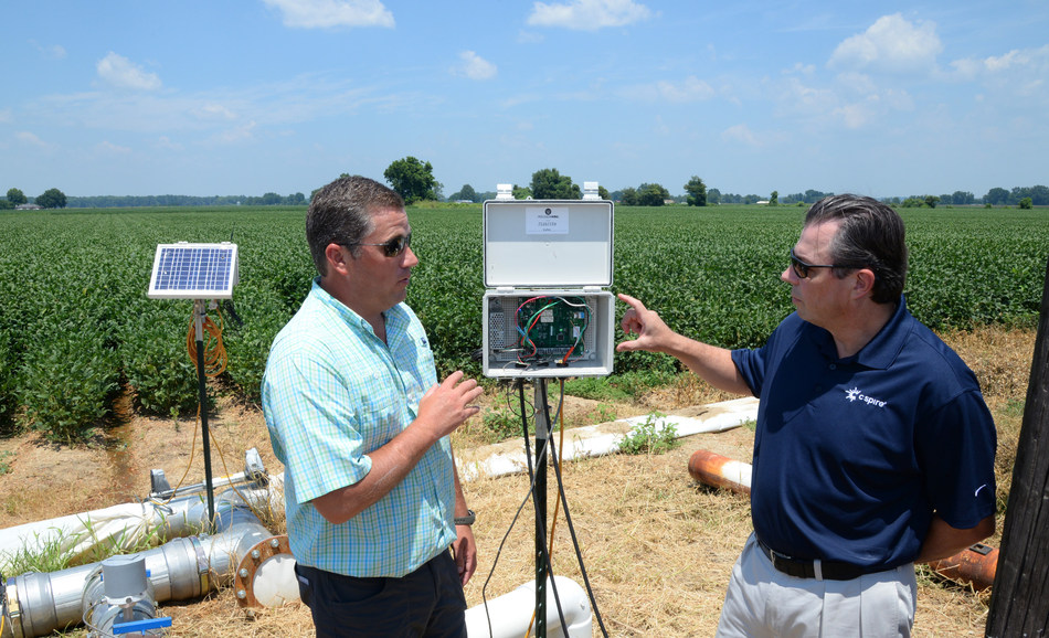 C Spire President Stephen Bye (right) and Nick King, CEO of Precision King, discuss an automated irrigation system controller that uses wireless technology to manage water usage at a soybean field near Tchula, Miss.