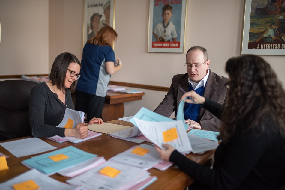 American Legion National Headquarters employees in Indianapolis, Ind. sort through Temporary Financial Assistance requests from members of the U.S. Coast Guard. Photo by Lucas Carter/The American Legion