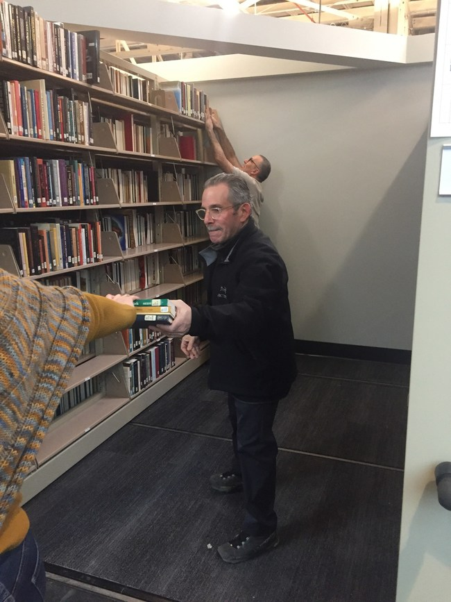 United Theological Seminary of the Twin Cities president Lew Zeidner helps move books into the new library.