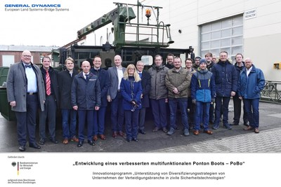"""General Dynamics European Land Systems employees in Germany pose in front of the """"PoBo"""" multifunctional, modular floating platform, designed to assist with civil protection and disaster release."""