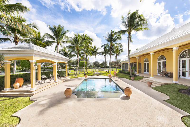 A courtyard-style pool enjoys gentle, natural breezes, and is surrounded by a large, paved terrace for plenty of sunbathing. More at WellingtonLuxuryAuction.com.