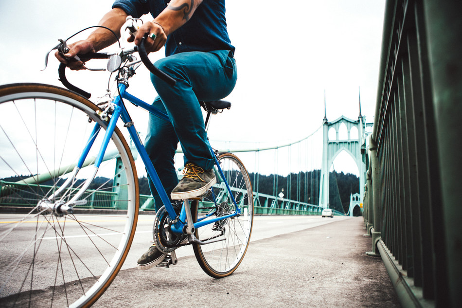An unrecognizable man commuting across the St John's Bridge in an urban city environment. He travels on his street bicycle into the city over the Saint John's Bridge. No face visible. Horizontal with copy space. (CNW Group/WESTJET, an Alberta Partnership)