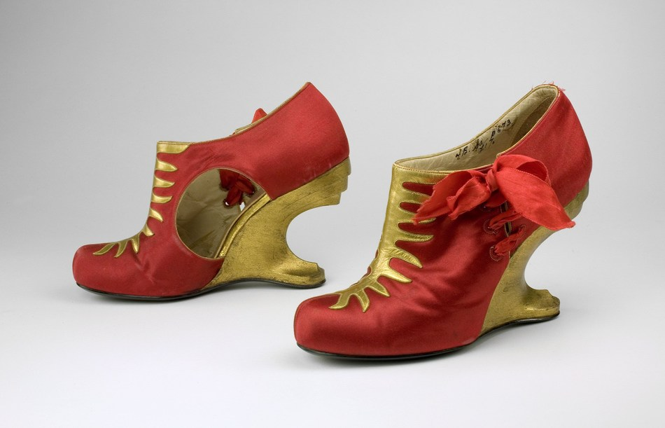 This glamourous pair of shoes, featuring carved wooden heels that rival Streamline Moderne sculpture and uppers in brilliant red silk and gold kid was sold by Delman and were most likely designed by Steven Arpad. In the 1930s, it was common for prominent shoe designers including Roger Vivier, André Perugia, and Arpad to be uncredited for designs they made for fashion houses.  Probably Steven Arpad for Delman. American, c. 1939. Collection of the Bata Shoe Museum. Image © 2019, Bata Shoe Museum, (CNW Group/Bata Shoe Museum)
