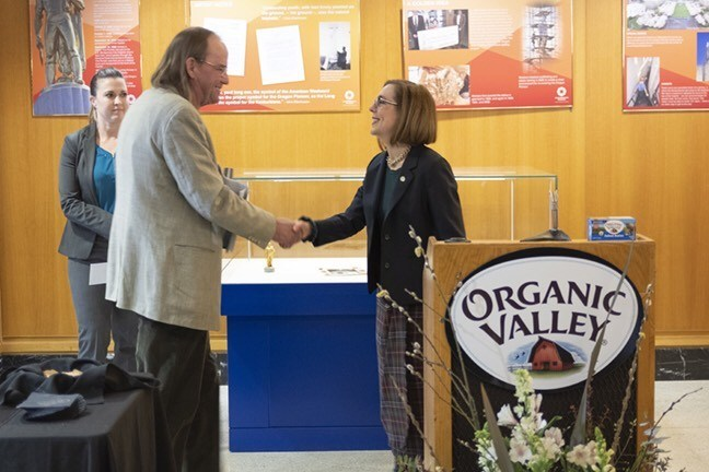 Organic Valley CEO and founding farmer George Siemon shakes hands with Oregon Governor Kate Brown