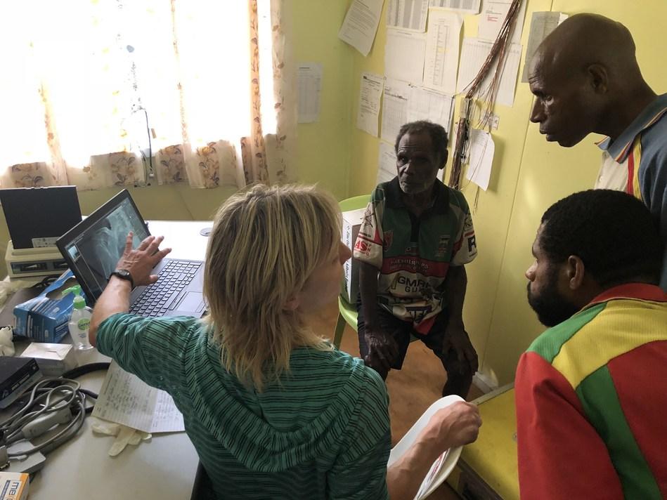 Dr. Carolyn Marquardt consulting with a patient and advising Community Health Workers regarding patient's x-ray image in Sapmanga village, YUS