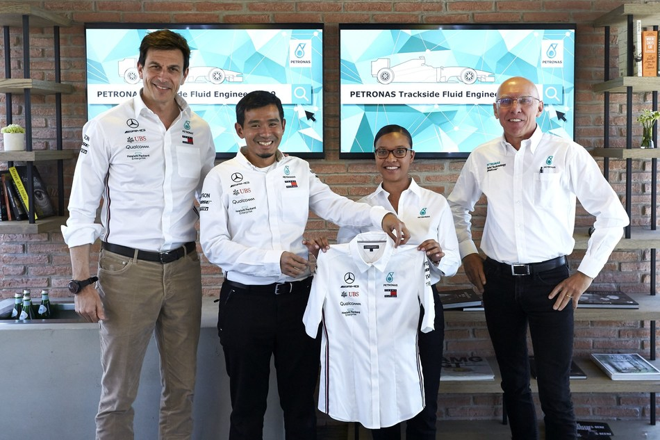 Circuit de Catalunya, Barcelona. Centre: Established PETRONAS Trackside Fluid Engineer (PTFE), Ahmad Nasri Mohd Shafie, presents Stephanie Travers with her team uniform. Far Right: Eric Holthusen, PLI Group Technology Officer. Far Left: Toto Wolff, Team Principal and CEO of Mercedes-AMG PETRONAS Motorsport. (PRNewsfoto/PETRONAS)