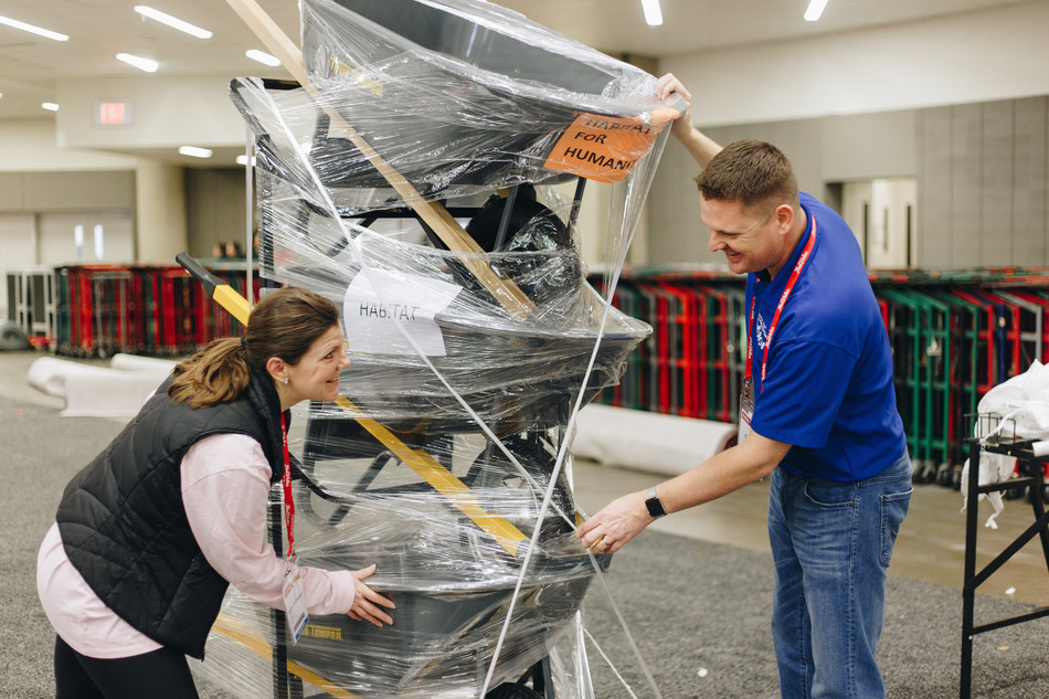 Cory Hohweiler, VP of Retail and Carmen Homes, VP of Development wrap newly donated ReStores products