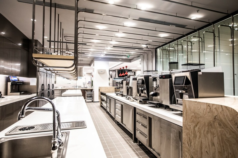 The beverage preparation area features a variety of coffee machines and spacious counters