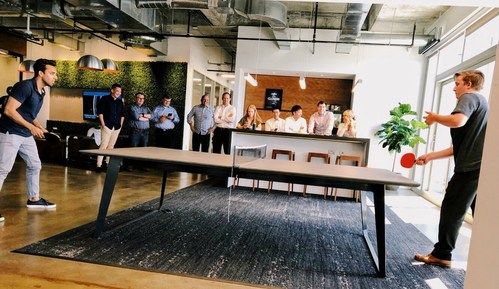 RESICAP employees enjoy a round of ping pong. A full game room, free snacks and Starbucks coffee, and a 'Never Settle' initiative are just some of the great perks that employees enjoy at the new office.