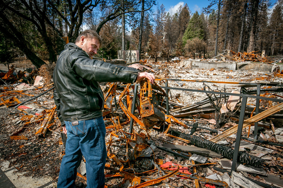 Walt Taber of the Paradise Medical Group looks at a burned computer in Paradise, Calif. on February 28th, 2019