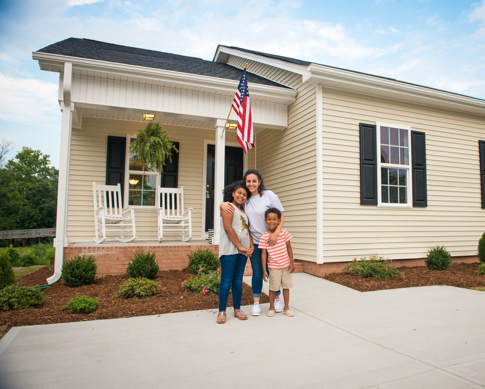 New homeowners in Raleigh, NC, happy to receive their new house keys. One of the nearly 500 homes built or remodeled through product donations by Ply Gem as part of the company's Home for Good project.
