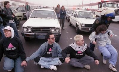 Foto de manifestantes de Stop AIDS Now or Else (SANOE) que bloquean el Puente Golden Gate, Rick Gerharter, Foto de manifestantes de Stop AIDS Now or Else (SANOE) que bloquean el Puente Golden Gate, 1989. Foto (PRNewsfoto/Oakland Museum of California)