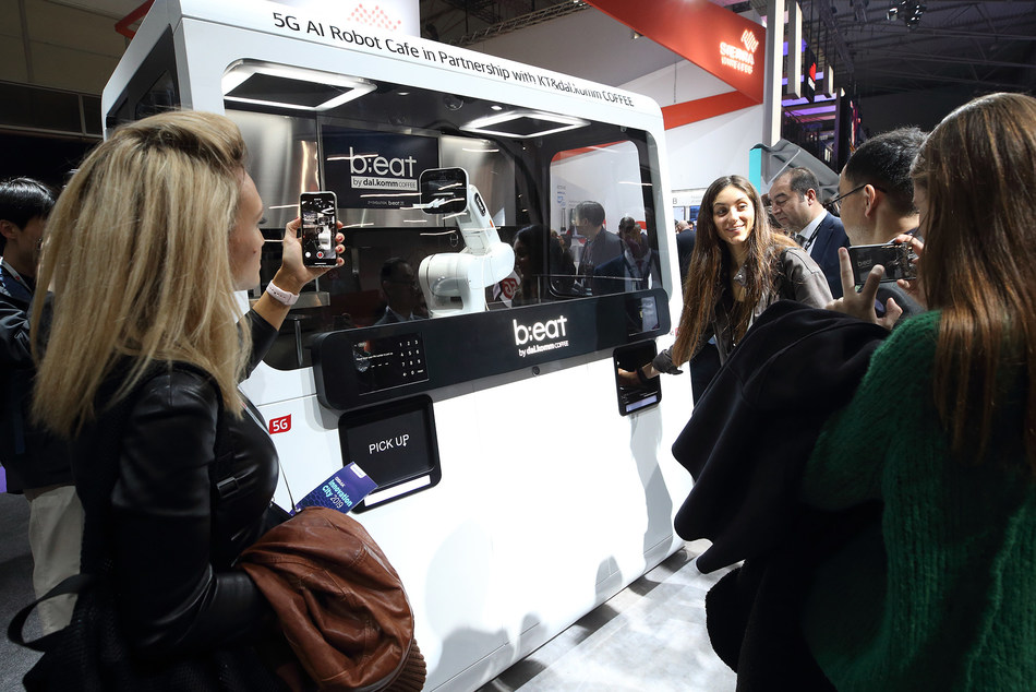 Visitors watch the 5G-powered AI robot cafe b;eat2E in action, which is co-developed by KT Corp. and Dal.Komm Coffee, at MWC 2019 held in Barcelona, Spain from Feb 25 to 28.